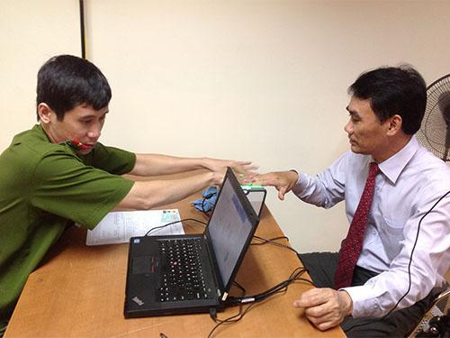 Ông Trần Đình Nhã, Phó Chủ nhiệm Ủy ban Quốc phòng - An ninh của Quốc hội, làm thủ tục cấp đổi CMND ngay bên lề hội thảo