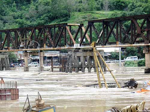 Nước lũ nhấn chìm cầu La Hai (đường bộ) và nhiều thiết bị của đơn vị xây cầu mới bên cạnh  Ảnh: Hồng Ánh
