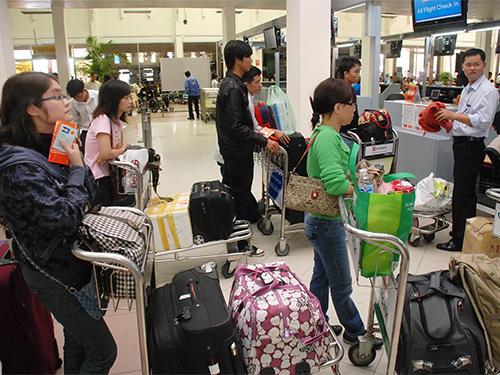 Xếp hàng chờ làm thủ tục tại sân bay Tân Sơn Nhất Ảnh: TẤN THẠNH