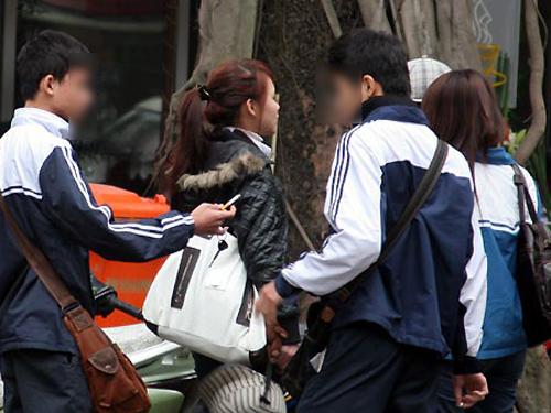 Học sinh hút thuốc lá trước cổng trường