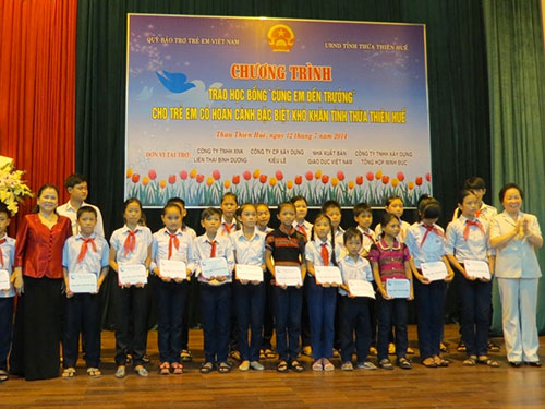 """Phó Chủ tịch nước Nguyễn Thị Doan (bìa phải) trao học bổng """"Cùng em đến trường"""" cho học sinh nghèo tại TP Huế"""