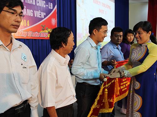 Bà Nguyễn Trần Phượng Trân, Phó Chủ tịch LĐLĐ TP HCM, trao cờ thi đua của LĐLĐ TP cho các tập thể xuất sắc