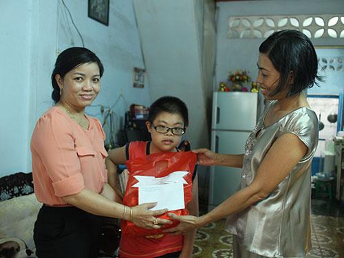 Bà Đinh Thị Thanh Thủy - Phó Chủ tịch LĐLĐ quận 3, TP HCM (trái) - trao quà cho bé Đặng Minh Khoa