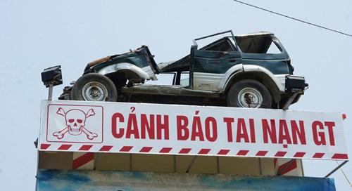 Biển cảnh báo tai nạn giao thông bằng ô tô con hư hỏng do bị tai nạn được ông Nguyễn Tiến Định dựng lên bên quốc lộ 1A và đường sắt Bắc-Nam