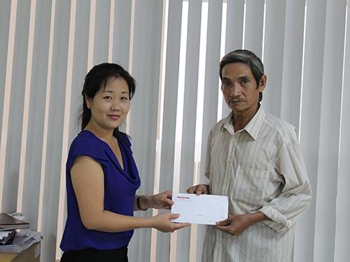 Đại diện Báo Người Lao Động trao tiền của bạn đọc giúp đỡ  gia đình ông Nguyễn Minh Quang