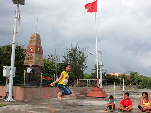 Những công dân nhí vui chơi dưới cột mốc chủ quyền ở xã đảo Song Tử Tây, huyện Trường Sa - Khánh Hòa. Ảnh: PHAN ANH