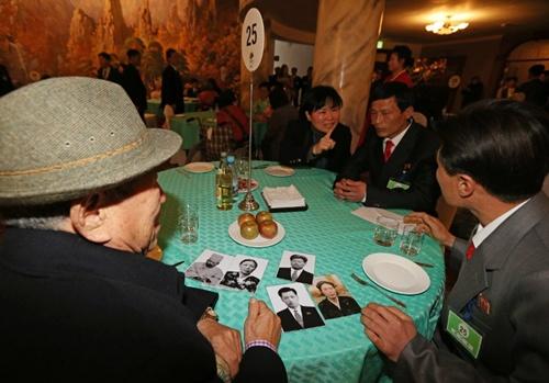Ông Na Bok-seop (đội mũ), người Hàn Quốc, nhìn những tấm ảnh khi ngồi cạnh cháu trai Na Ki-jun, người Triều Tiên. Ảnh: Yonhap