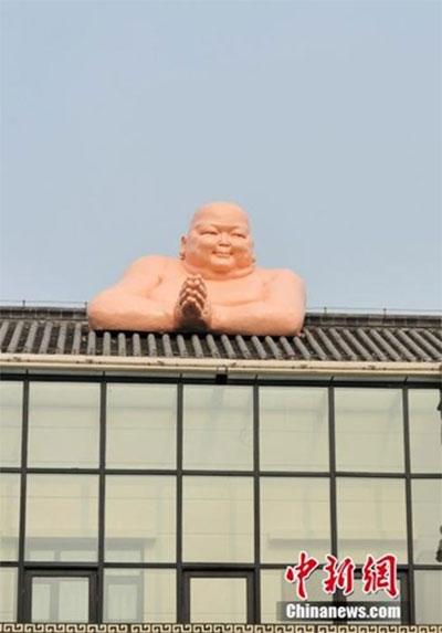 """Trung Quốc dỡ bỏ tượng """"Đức phật khỏa thân"""" trèo tường"""