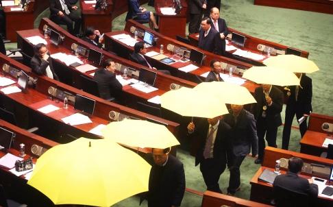 27 nhà lập pháp ủng hộ dân chủ xòe chiếc ô màu vàng rời khỏi Hội đồng lập pháp. Ảnh: SCMP