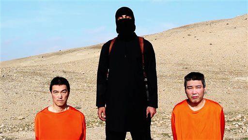 Chiến binh IS cùng 2 con tin Nhật Bản trong đoạn video đăng tải hôm 20-1. Ảnh: AP