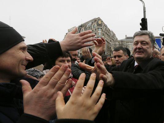 Tổng thống Ukraine Petro Poroshenko (bìa phải) tham dự lễ diễu hành hôm 22-2. Ảnh: AP