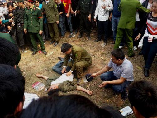 Người đàn ông bị ngã từ trên cây đánh đu xuống dưới đất, bị ngất đi. Có rất đông du khách hiều kỳ đứng vây quanh - Ảnh: oto fun