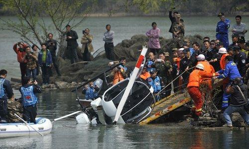 Chiếc trực thăng của ông Li đang được trục vớt đưa vào bờ. Ảnh: CFP