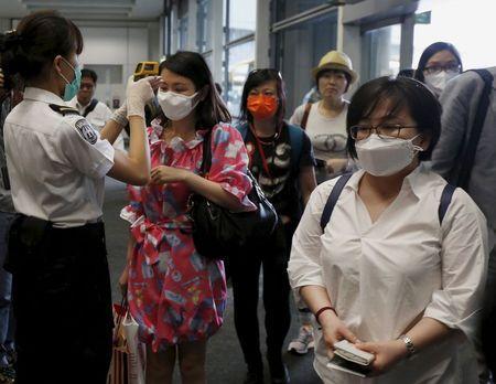 Nhân viên một sân bay ở TP Busan kiểm tra thân nhiệt hành khách. Ảnh: Reuters
