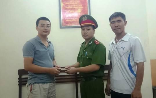 Anh Nguyễn Tiến Công (bìa trái) may mắn nhận được chiếc ví đánh rơi từ công an