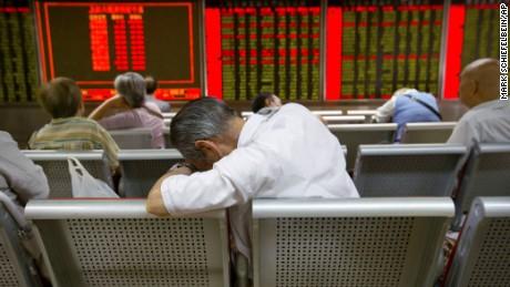Nhà đầu tư Trung Quốc uể oải theo dõi chỉ số chứng khoán tại Bắc Kinh. Ảnh: AP