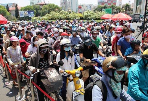Hàng ngàn người ngồi trên xe đội nắng đợi đến lượt để nhận thức ăn miễn phí Ảnh: LÊ PHONG