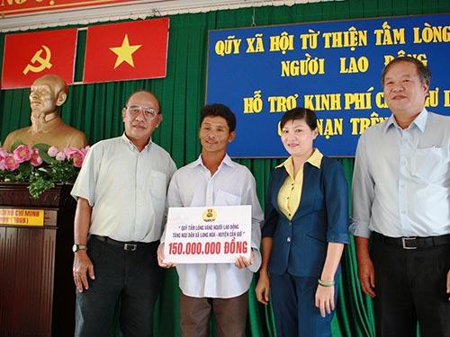 Ông Nguyễn Thọ Trung (trái), Phó Giám đốc Quỹ Tấm lòng vàng Người Lao Động, trao tiền cho ngư dân xã Long Hòa