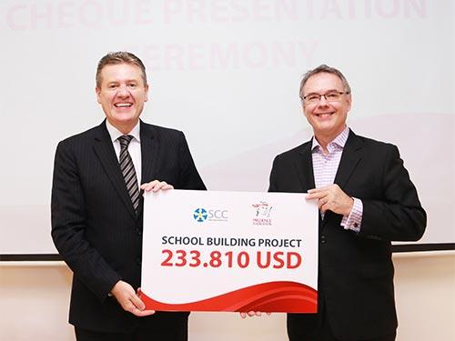 Ông Wilf Blackburn, Tổng Giám đốc Prudential Việt Nam (trái), trao tiền xây dựng trường học cho ông Tim Mullet, Giám đốc Saigon Children's Charity Ảnh: PRUDENTIAL