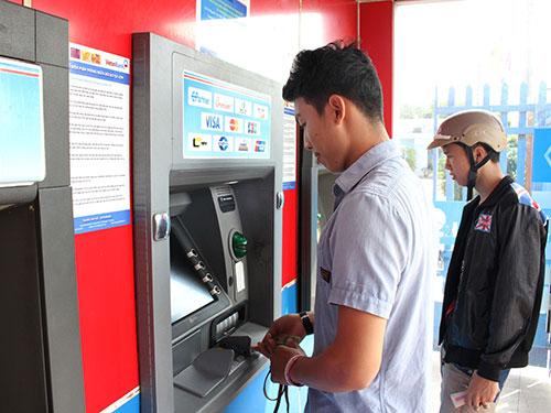 Khách hàng rút tiền qua hệ thống máy ATM. (Ảnh chỉ có tính minh họa) Ảnh: HOÀNG TRIỀU
