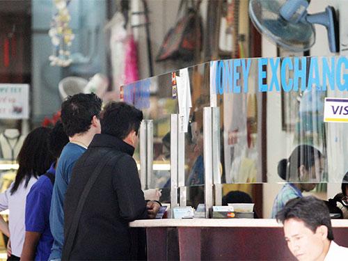 Một điểm thu đổi ngoại tệ trên đường Đồng Khởi, quận 1, TP HCM Ảnh: HOÀNG TRIỀU