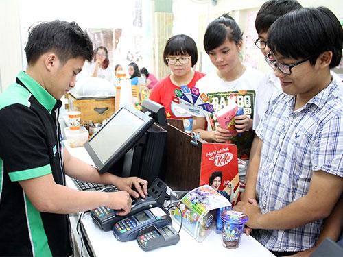 Khách mua hàng thanh toán qua thẻ tại Family Mart trên đường Lê Quý Đôn, quận 3, TP HCM.  (Ảnh chỉ có tính minh họa) Ảnh: HOÀNG TRIỀU