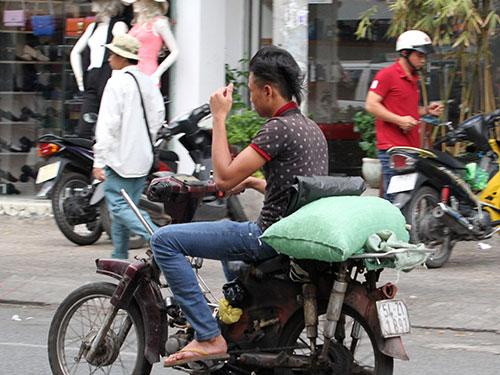 Nhiều nhân viên giao đá chạy xe máy chỉ còn trơ khung, nước đá đựng trong bao không bảo đảm vệ sinh. Ảnh: HOÀNG TRIỀU