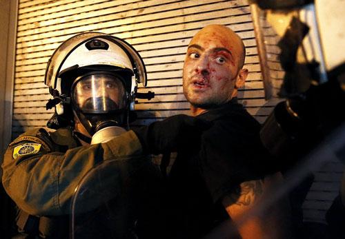 Một người chống đối bị bắt sau vụ xô xát ở thủ đô Athens đêm 15-7Ảnh: REUTERS