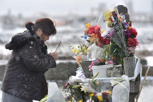 Một phụ nữ cầu nguyện cho các nạn nhân động đất, sóng thần ở tỉnh Miyagi hôm 11-3 Ảnh: MAINICHI