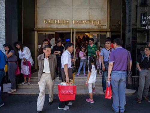 Du khách Trung Quốc bên ngoài một cửa hàng ở thủ đô Paris - Pháp Ảnh: CHINA.ORG.CN