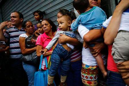 Nhiều người xếp hàng ẵm theo con nhỏ để có cớ chen lên vị trí đầu Ảnh: REUTERS