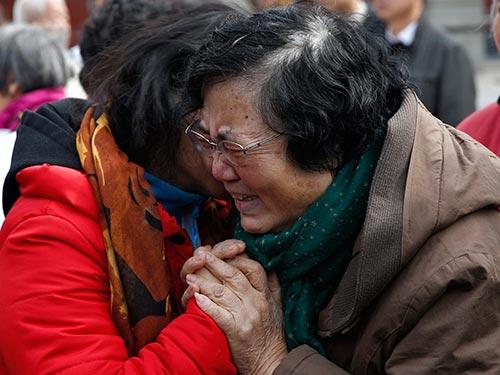 Người thân của những hành khách trên chuyến bay MH370 an ủi nhau tại buổi lễ tưởng niệm ở thủ đô Bắc Kinh - Trung Quốc hôm 8-3 Ảnh: REUTERS