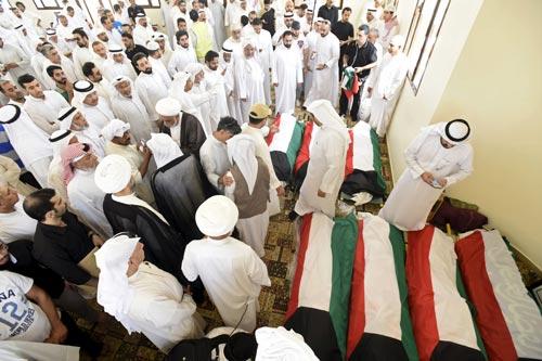 Cờ Kuwait phủ lên thi thể các nạn nhân vụ đánh bom tại nghĩa trang Al Jafariya ở Kuwait ngày 27-6  Ảnh: REUTERS