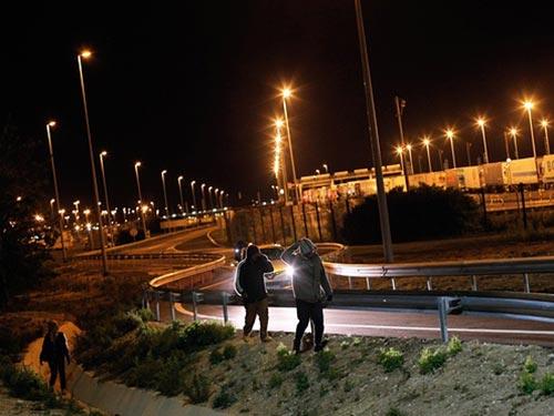 Người di cư đi bộ bên ngoài khu vực do Eurotunnel quản lý ở TP Calais - Pháp đêm 28-7 Ảnh: AP