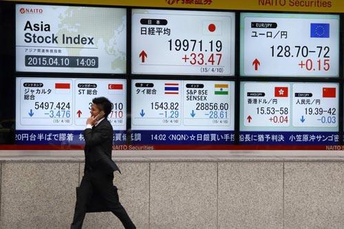 Người dân đi ngang bảng chứng khoán điện tử bên ngoài một công ty chứng khoán tại Tokyo Ảnh: BLOOMBERG