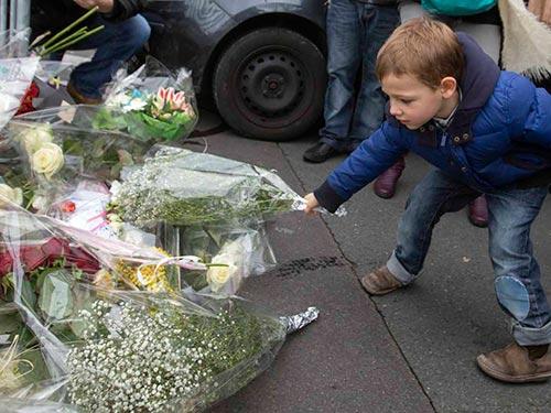 Một bé trai đặt hoa tưởng niệm nạn nhân vụ bắt con tin ở Porte de Vincennes, phía Đông Paris Ảnh: REUTERS