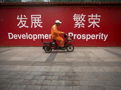 """Một công nhân Trung Quốc chạy xe qua tấm bảng lớn có chữ """"Phát triển"""" và """"Thịnh vượng"""" trên đường phố Bắc Kinh hôm 15-7 Ảnh: AP"""
