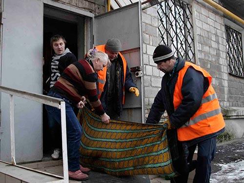 Cư dân TP Donetsk mang thi thể một người chết do đạn pháo đi chôn Ảnh: REUTERS