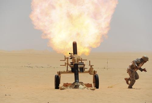 Một binh sĩ Ả Rập Saudi bắn đạn pháo về phía vị trí của phiến quân Houthi tại biên giới với Yemen Ảnh: REUTERS