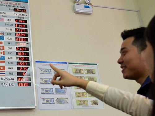 Khách hàng theo dõi tỉ giá tại Ngân hàng TMCP Đông Á sáng 7-1 Ảnh: Tấn Thạnh