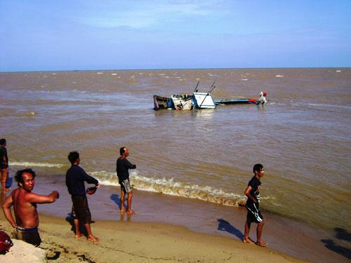 Ngư dân đang tìm cách đưa vào bờ một tàu cá bị sóng đánh chìm trên biển Phú Yên Ảnh: HỒNG ÁNH