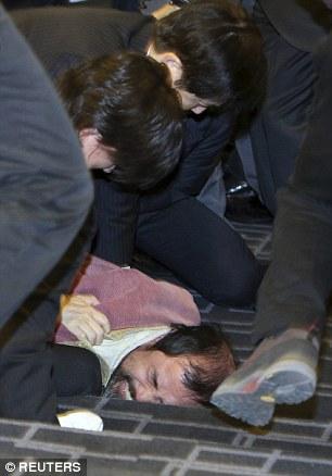 Họ Kim bị cảnh sát khống chế. Ảnh: Reuters
