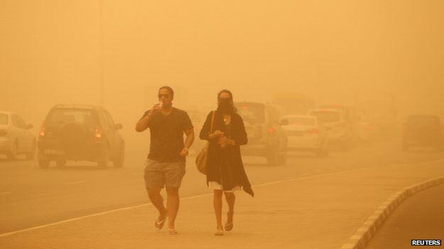 Không khí tràn ngập màu vàng của cát sa mạc. Người dân cảm thấy khó thở khi di chuyển trên đường. Ảnh: Reuters