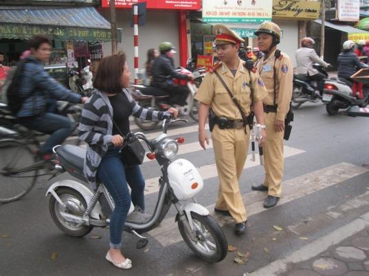 Yêu cầu người đi xe đạp điện không đội mũ bảo hiểm về vị trí xử lý vi phạm