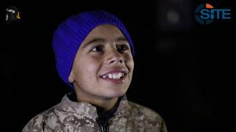Đứa trẻ khoảng 8 tuổi mỉm cười trong đoạn video của IS. Ảnh: Twitter
