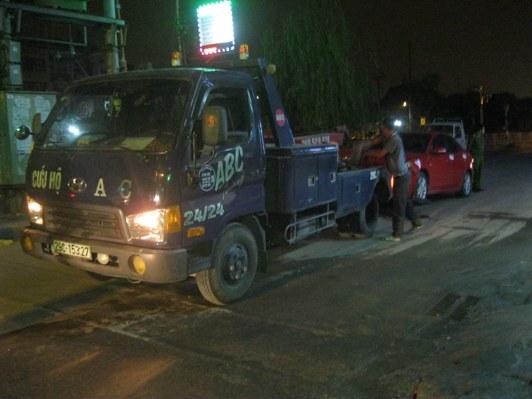 Xe cứu hộ đang đưa xe ô tô 4 chỗ đi khỏi hiện trường