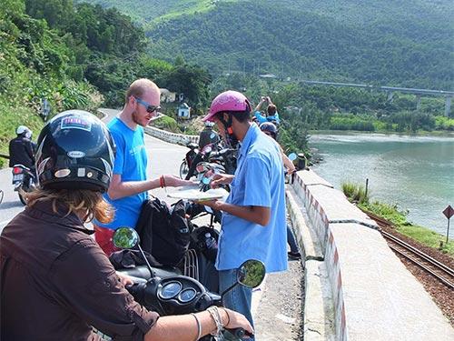 Du khách nước ngoài bị chèo kéo mua bản đồ ở chân đèo Hải Vân (địa phận tỉnh Thừa Thiên - Huế)Ảnh: THIÊN KIM