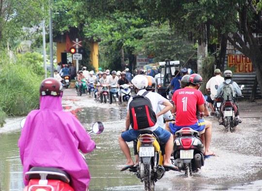 Người dân khó khăn di chuyển qua vũng nước đen trên đường Linh Đông (quận Thủ Đức) để về nhà sau giờ tan tầm