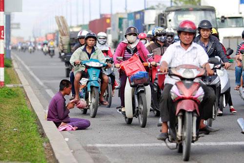 Một người xin ăn bên vệ đường đầy xe cộ trên xa lộ Hà Nội Ảnh: HOÀNG TRIỀU