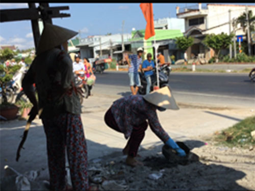 Bà Châu Thị Ba cầm cây canh giữ cho bà Nguyễn Thị Liên xúc các mẻ hồ đổ đi, không cho bà Liên Mỹ Lén sửa nhà